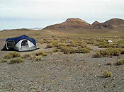 Two tents are separated by sand and sage along the desert floor.